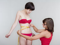 Young women measuring Royalty Free Stock Image