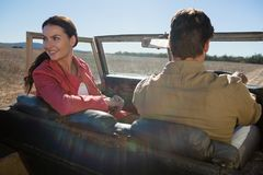 Woman with man looking away in off road vehicle. Young women with men looking away in off road vehicle on landscape Stock Image