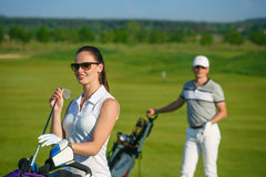 Young women and men playing golf Stock Images