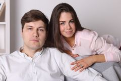 Young woman and man pose together on armchair Stock Images