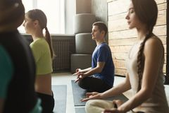 Young women and man in yoga class, relax meditation pose Royalty Free Stock Photo
