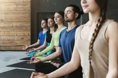 Young women and men in yoga class, relax meditation pose. Young women and men in yoga class, meditation exercises. Lotus pose for relaxation. Healthy lifestyle stock images