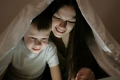 Young woman mom and her son watching a film together on tablet under the blanket. Young women mom and her son watching a film together on tablet under the Royalty Free Stock Photo