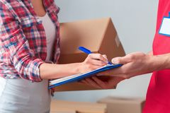 Young girl moving to new place standing with delivery man signing form close-up royalty free stock images