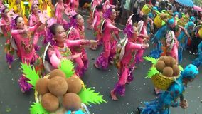 Young women in ornate coconut costume dance along the street, a festival to honor a patron saint. San Pablo City, Laguna, Philippines - January 13, 2014: Young