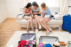 Young women packing suitcases for vacation and using smartphones at home, Stock Images