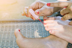 Young women are painted toenails. With red nail polish Stock Image