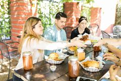 Friends Sharing Food During Reunion Party. Young women passing cooked meat to friend during social gathering at restaurant royalty free stock image