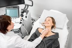 Woman during the ultrasound examination. Young women patient during the ultrasound examination of a thyroid lying on the couch in medical office royalty free stock photo