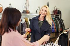 Young woman paying by credit card. Young women paying to shop assistant by credit card and receiving shopping bags in store. Credit card shopping concept Royalty Free Stock Photo
