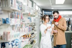 Pharmacist with client in the pharmacy store. Young women pharmacist choosing medicine with male client dressed in coat and scarf in the pharmacy store royalty free stock image