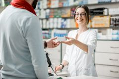 Pharmacist selling medications in the pharmacy store. Young women pharmacist giving medications to the male client standing at the paydesk of the pharmacy store Royalty Free Stock Image