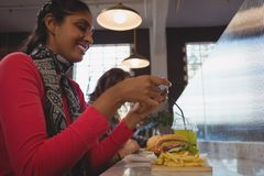 Woman photographing French fries in cafe. Young women photographing French fries at counter in cafe Royalty Free Stock Photo
