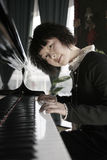 Young women with piano Stock Images