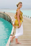 Young women on a pier. Young women standing alone on a pier. Indian ocean, Maldives Stock Image