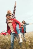 Young women piggybacking on boyfriends. In flower field royalty free stock photo