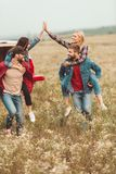 Young women piggybacking on boyfriends and giving high five. In flower field stock photo