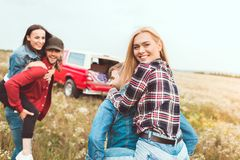 Young women piggybacking on boyfriends and looking at camera. In field royalty free stock photo