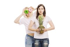 Young women with pineapple and cakes in their hands, a difficult choice. Isolated on white background stock images