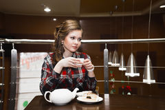 Young women in a plaid shirt drinking tea in a cafe Royalty Free Stock Image