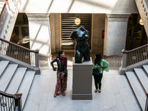 Young women play around Maillol sculpture in Chicago Art Institu Stock Photo