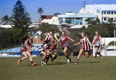 Young women play Australian Rules Football Royalty Free Stock Images