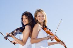 Young women play violins Stock Image