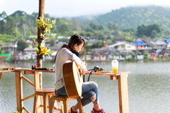 Young women playing acoustic guitar Royalty Free Stock Photos