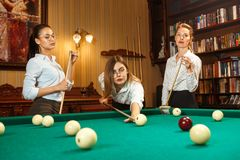 Young women playing billiards at office after work. Young smiling women playing billiards at office or home after work. Business colleagues involving in Stock Images