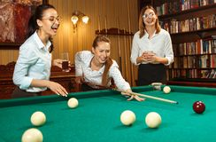 Young women playing billiards at office after work. Young smiling women playing billiards at office or home after work. Business colleagues involving in Royalty Free Stock Photos