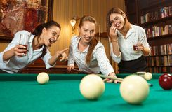 Young women playing billiards at office after work. Young smiling women playing billiards at office or home after work. Business colleagues involving in Royalty Free Stock Image