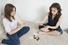 Young women playing cards while sitting on fur sofa Royalty Free Stock Photo