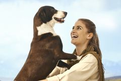 Young women playing with dog outdoors Stock Photos