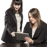 Young women playing on Ipad. With expressive faces Royalty Free Stock Photos