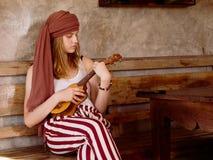 Young women plays on ukulele Stock Photo