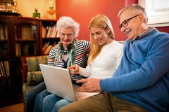 Young woman pointing on computer and showing to grandparetns images. Young women pointing on computer and showing to grandparetns images at vacation stock images