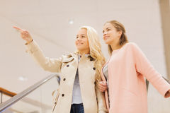 Young women pointing finger on escalator in mall Royalty Free Stock Image