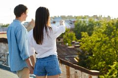 Something curious. Young women pointing forwards while holding her boyfriend by hand during roof date stock photo