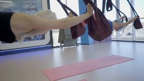 Young women practice anti gravity yoga in hammock in studio. stock footage