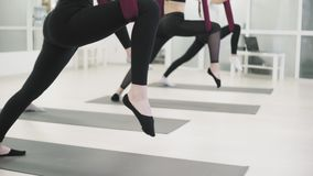 Young women is practicing aero yoga in sports club. women stretches legs. 4K stock video footage
