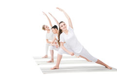 Young women practicing Extended Side Angle Pose on yoga mats Royalty Free Stock Photography