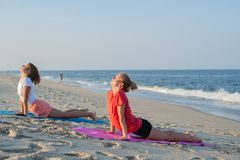 Young women practicing yoga on the beach. Beautiful girls practicing yoga Cobra exercise stock photography