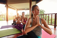 Young women practicing yoga in half spinal twist pose. Shot of young women practicing yoga in half spinal twist pose with their hands joined. Young people in Stock Photography