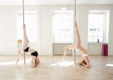Young women practising pole dance in a pole fitnes Royalty Free Stock Images
