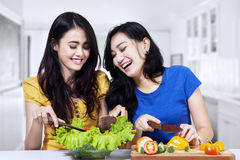 Young women prepare salad together. Young asian women prepare salad together in the kitchen Royalty Free Stock Photo