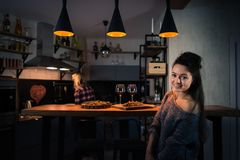 Young women preparing dinner in the modern home kitchen in the evening. Blonde staying back on the background. Food and wine on the bar counter at the stylish Royalty Free Stock Image