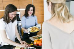 Young women preparing healthy food in kitchen. Young happy women preparing healthy food in the kitchen royalty free stock photo