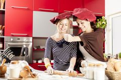 Young women in the kitchen. Young women preparing meal in the kitchen Royalty Free Stock Photos