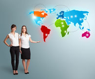 Young women presenting colorful world map Royalty Free Stock Photography