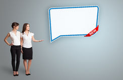 Young women presenting modern speech bubble copy space Royalty Free Stock Photography